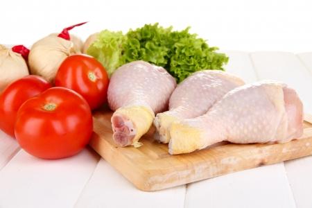 Jambes de poulet cru sur planche de bois de près