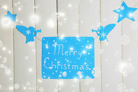 Signboard with words Merry Christmas on wooden table background close-up photo