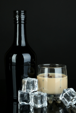 baileys: Baileys liqueur in bottle and glass isolated on black Stock Photo