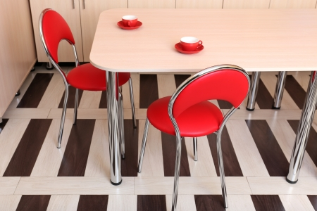 Modern red chairs near table in kitchen photo