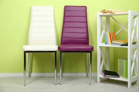houseware: Beautiful interior with modern  color chairs,  books on wooden stand, on wall background