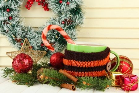 Cup of hot cacao with Christmas decorations on table on wooden background photo