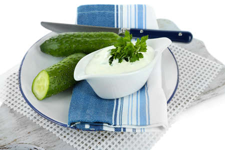 Cucumber yogurt in sauceboat, on color napkin, isolated on white photo