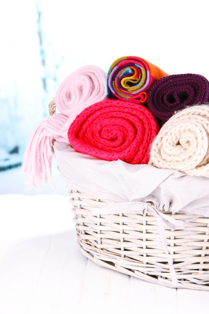 clothes interesting: Warm knitted scarves in basket on winter background
