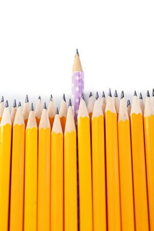 Crayon de célébration parmi les crayons habituels, isolés sur fond blanc