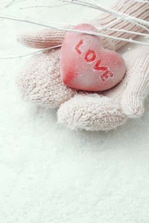 mittens: Female hands in mittens with red heart, close-up