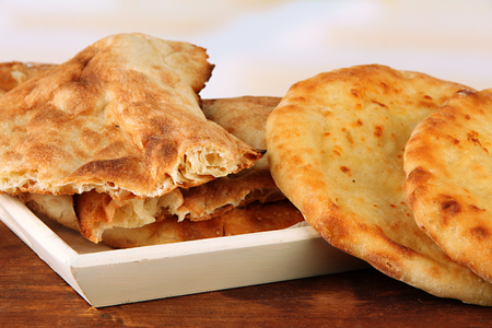 Pita breads on tray on table on bright background photo