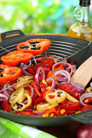 Vegetables in wok on wooden table on natural background photo