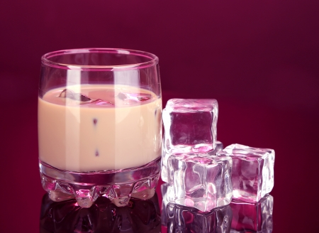 Baileys liqueur in glass on pink background photo
