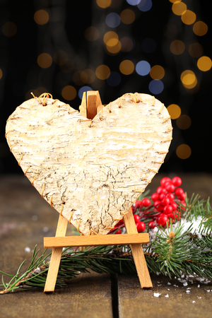 Decorative heart on easel, on wooden table, on shiny background photo