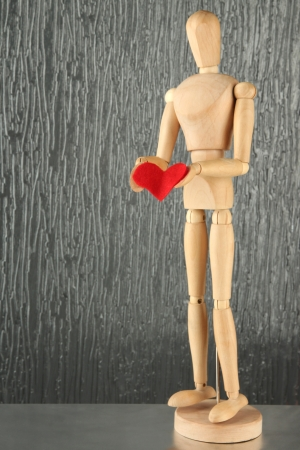 Wooden mannequin holding red heart on gray background photo