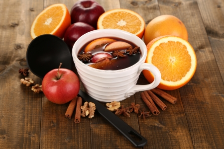 rich flavor: Fragrant mulled wine in bowl on wooden table close-up