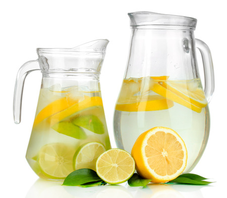 Cold water with lime, lemon and ice in pitchers isolated on white