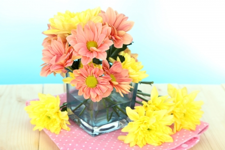 Chrysanthemum flowers in vase on wooden table on natural background photo