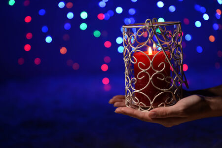 Candle in hand on blur lights background photo