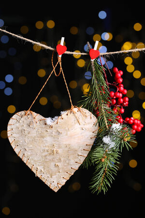 Decorative heart on rope on shiny background photo