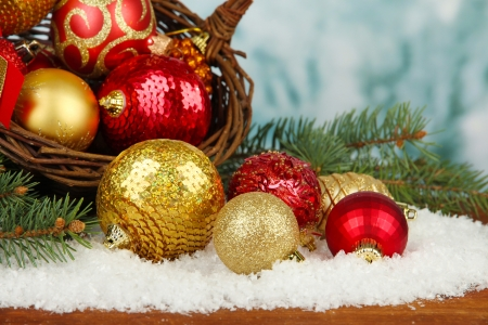 Christmas decorations in basket with snow on table on bright background photo