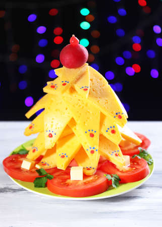 Christmas tree from cheese on table on dark background photo