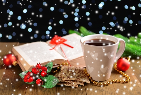 Composition of book with cup of coffee and Christmas decorations on table on dark background photo