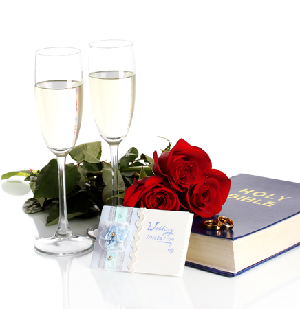 Wedding rings on bible with roses and glasses of champagne isolated on white photo