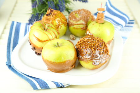 Homemade taffy apples, on napkin, on wooden background photo