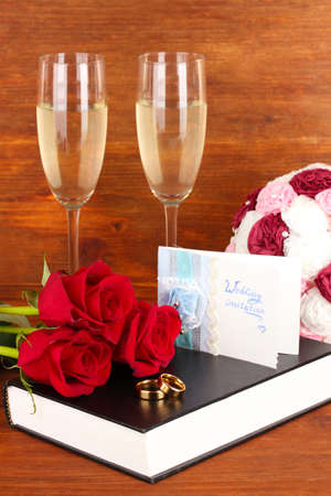Wedding rings on bible with roses and glasses of champagne on wooden background photo