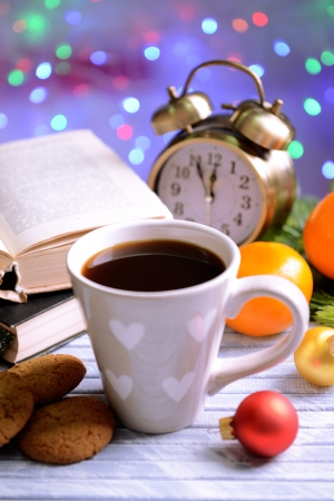 Composition of book with cup of coffee and Christmas decorations on table on bright background photo