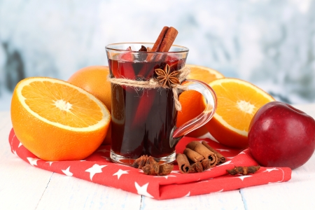 Fragrant mulled wine in glass on napkin on winter background