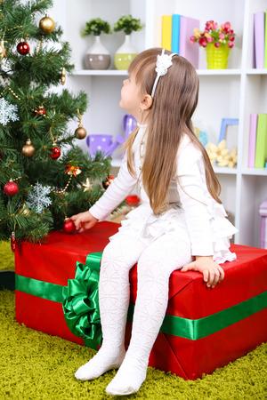 Little girl setting on big present box near Christmas tree in room Фото со стока