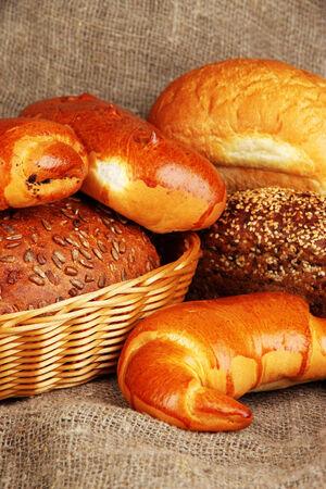 Baked bread in wicker basket on burlap background photo