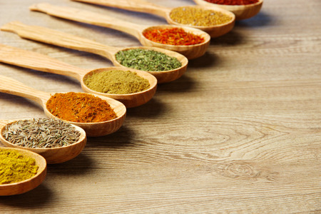 close up food: Assortment of spices in wooden spoons on wooden background