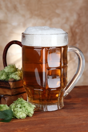 Glass of beer and hops, on wooden table photo