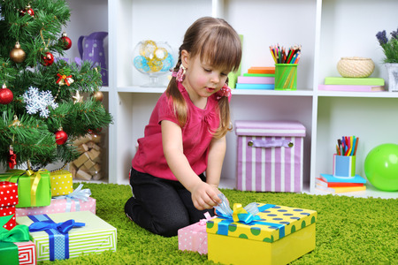 Little girl with present box near Christmas tree in room photo