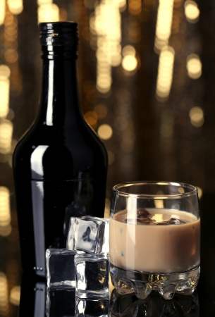 Baileys liqueur in bottle and glass on golden background photo