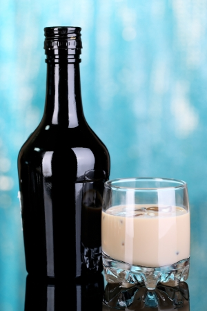 baileys: Baileys liqueur in bottle and glass on blue background