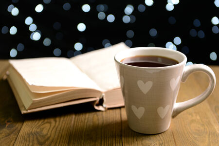 Composition of book with cup of coffee on table on dark background photo