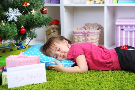 Little girl sleeping near Christmas tree in room photo