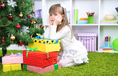 Little girl with presents near Christmas tree in room photo