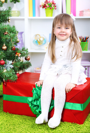 Little girl setting on big present box near Christmas tree in room photo