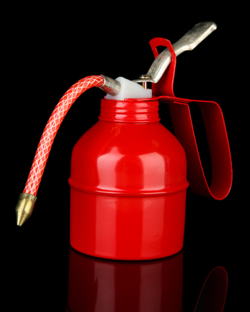 lubricator: Red oil can, isolated on black Stock Photo