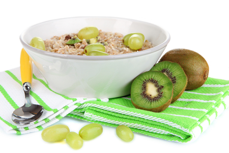 Useful oatmeal in bowl with fruit isolated on white
