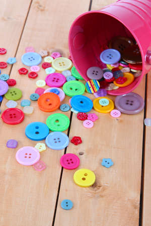 Colorful buttons strewn from bucket on wooden background photo