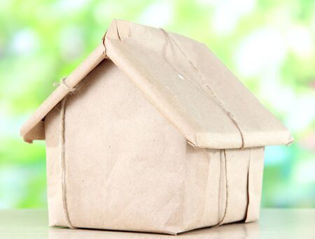 House wrapped in brown kraft paper, on nature background photo