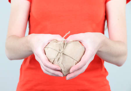 Woman hands holding a heart wrapped in brown kraft paper photo