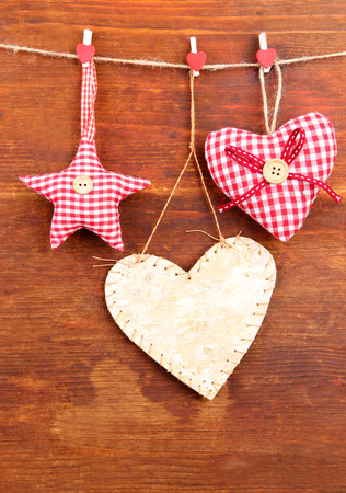 Decorative heart and star on rope, on wooden background photo