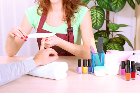 Girl manicurist doing manicure for man in beauty salon  photo