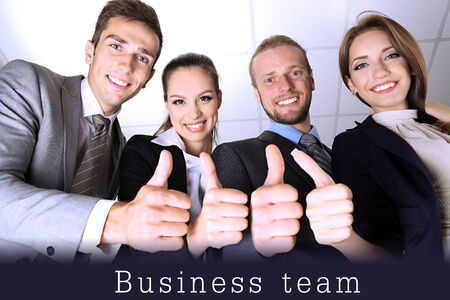 Business team showing thumbs up in office photo