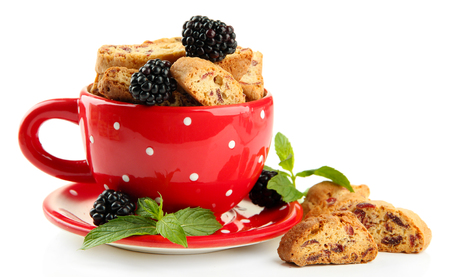 Tasty cookies with blackberry in cup isolated on white photo