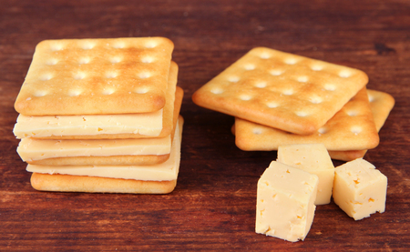 Delicious crackers with cheese on wooden background photo