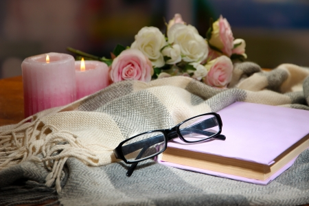 Composition with old book, eye glasses, candles and plaid on dark background photo